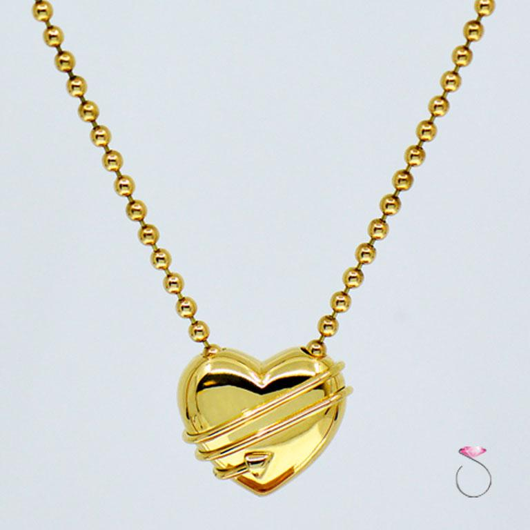 Authentic Tiffany & co. Cupid Heart & Arrow pendant with chain 18k yellow gold bead chain. The 18K yellow gold puff heart pendant measures approximately 19.60 mm x 16.70 mm x 9.75 mm. The pendant is attached to a beautiful 16 inch bead chain with a