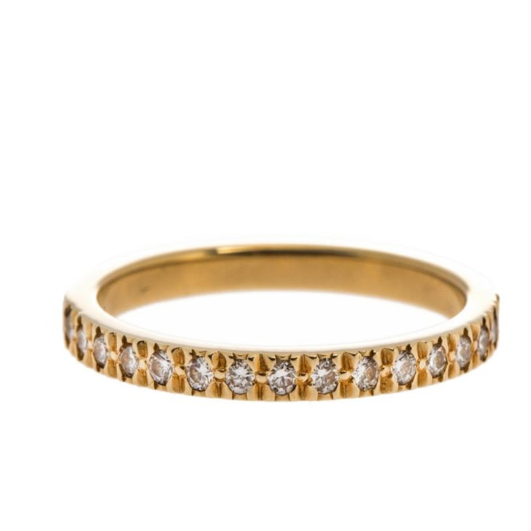 A beautiful ring to hold and treasure is this one by Tiffany & Co. Sculpted using 18k yellow gold, the precious band has a smooth finish and a breathtaking display of diamonds on the top. The gemstones shimmer wondrously and blend perfectly with the