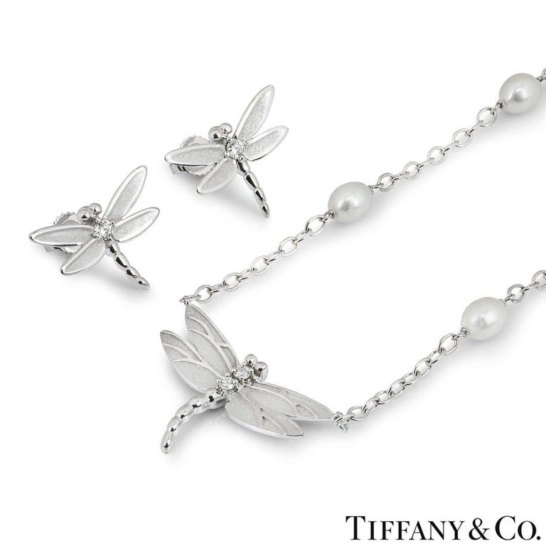 A beautiful necklace and earring suite by Tiffany & Co. The earrings are each set with a single round brilliant cut diamond in the centre of the Dragonfly and feature post and butterfly back fittings. The necklace has two round brilliant cut