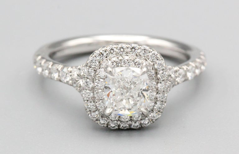 Elegant diamond and platinum engagement ring by Tiffany & Co. It features high grade round brilliant cut diamonds throughout with the central stone being 0.56ct, F color, VVS2 clarity. Ring size 5.5.  Hallmarks: Tiffany & Co., PT 950, 0.56ct,