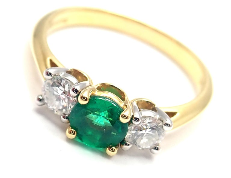18k Yellow Gold And Platinum Diamond Emerald Three Stone Band Ring. With 2 round brilliant cut diamonds VS1 clarity, G color total weight approx. .36ct 1 round emerald total weight approx. .50ct Measurements: Ring Size: 7 Weight:  3.4 grams Width at