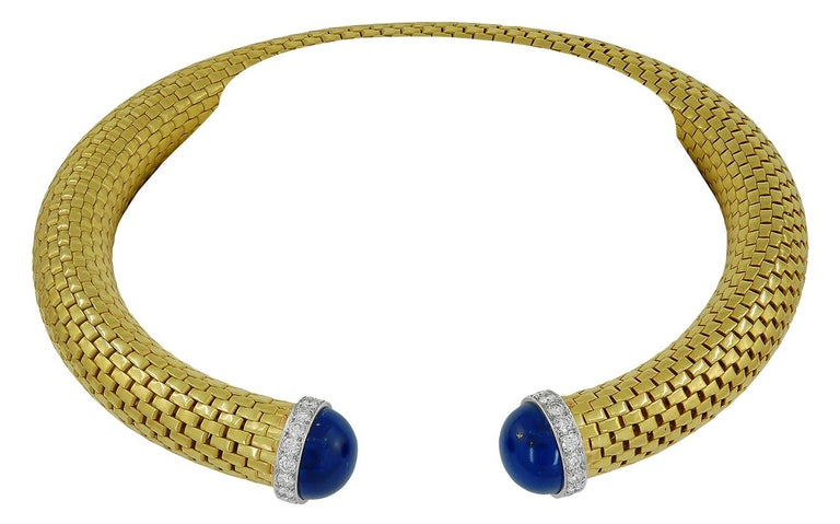 Exuding style and sophistication, comprising a rare 1970's Paloma Picasso Tiffany & Co necklace crafted in an 18k yellow gold mesh design, centering two cabochon lapis lazuli surrounded by a frame of brilliant diamonds, mounted in platinum. Made in