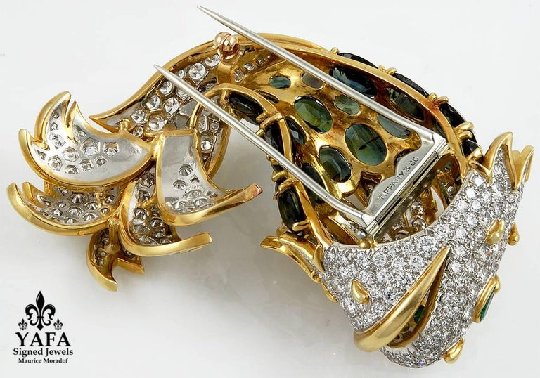 A 1970's Tiffany brooch designed as a stylized fish; its head and tail set with brilliant-cut diamonds, accented with raised gold piping, around a body set with oval-shaped peridots.  Signed Tiffany & Co.