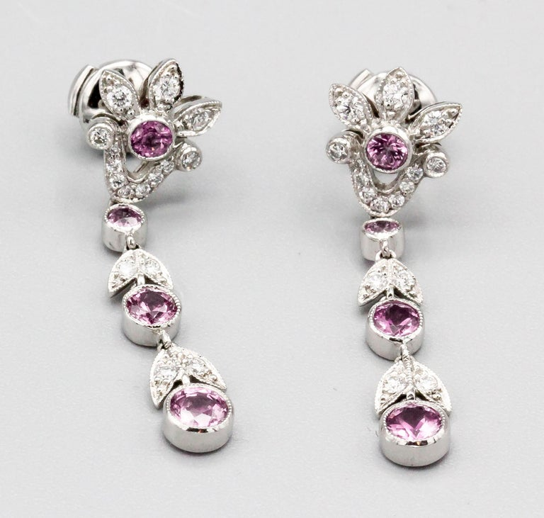 Fine pair of diamond, pink sapphire and platinum ear pendants by Tiffany & Co. The earrings feature a foliage design with approx. 1.5 carats of pink sapphires and .75 carats of round white diamonds.  With original box.  Hallmarks: T & Co., PT950.