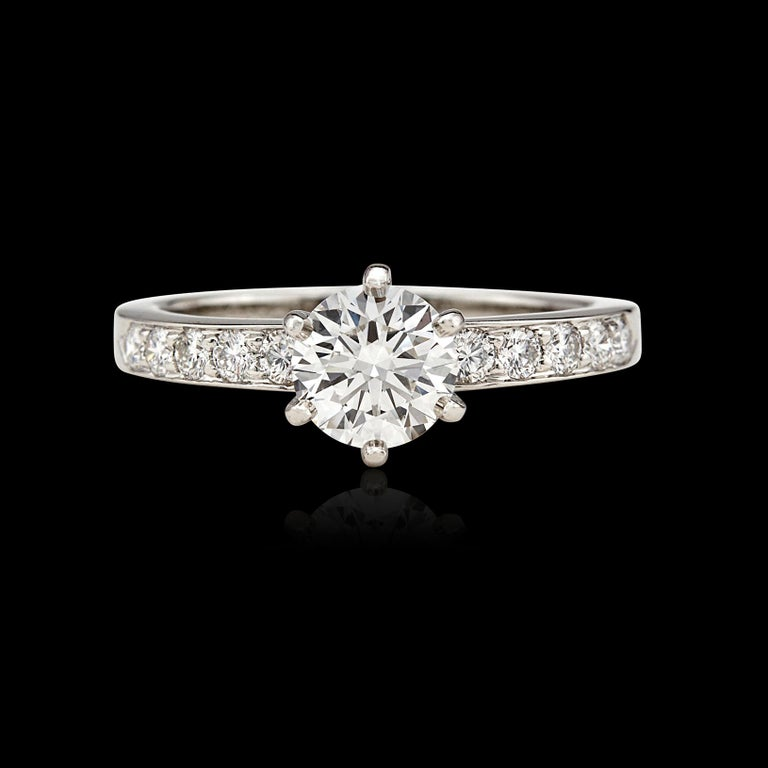 Classic quality and timeless beauty! This platinum Tiffany engagement ring features an 0.85-ct. round brilliant-cut diamond, G/VVS2 quality, set in 6-prongs and accented down the shoulders with 10 smaller round brilliant-cut diamonds, giving the