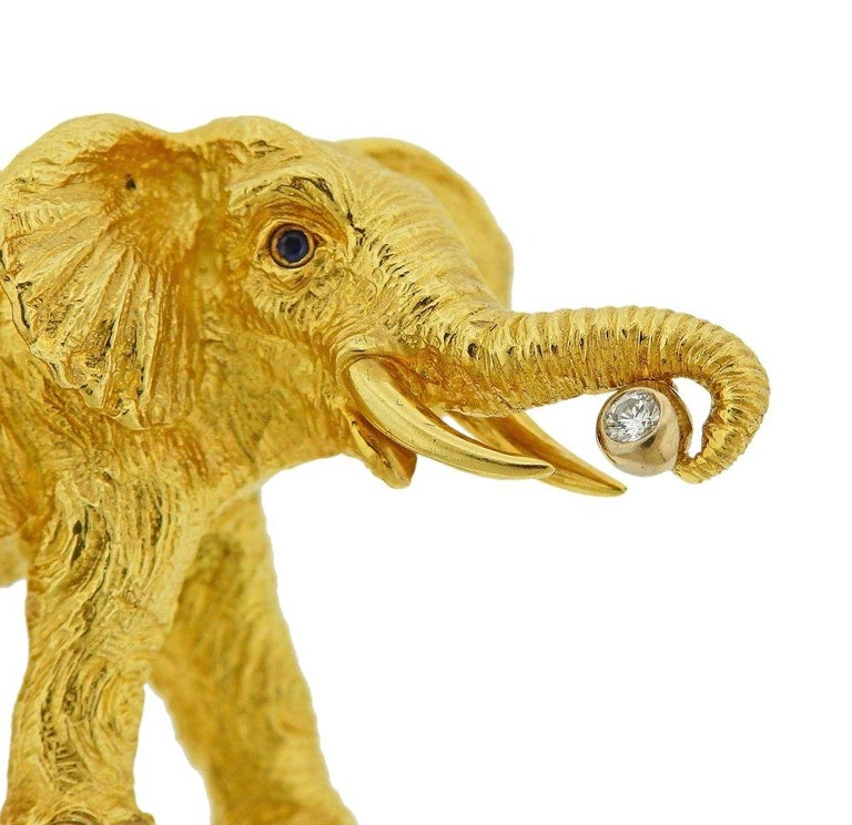 Tiffany & Co 18k gold elephant brooch, set with sapphire eyes and approx. 0.05ct G/VS diamond. Brooch is 49mm x 29mm. Weight is 29.9 grams. Marked Tiffany & Co, 1996, 750, Germany.