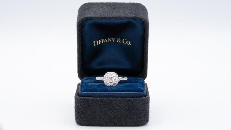 Tiffany & Co. Soleste engagement ring with an Excellent cut 0.49 ct cushion center , F Color, VS1 clarity finely crafted in a platinum double row halo design with round brilliant cut bead set diamonds. Includes Original Tiffany Certificate and