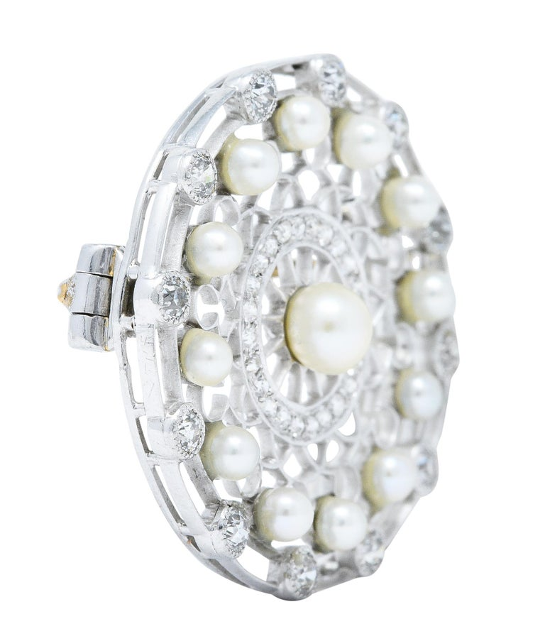 Circular brooch features a pierced trellis design and centers a 4.5 mm button pearl  Surrounded by a halo of 2.5 mm pearls - all are white to cream in color with very good luster  Accented by two concentric halos of old European cut