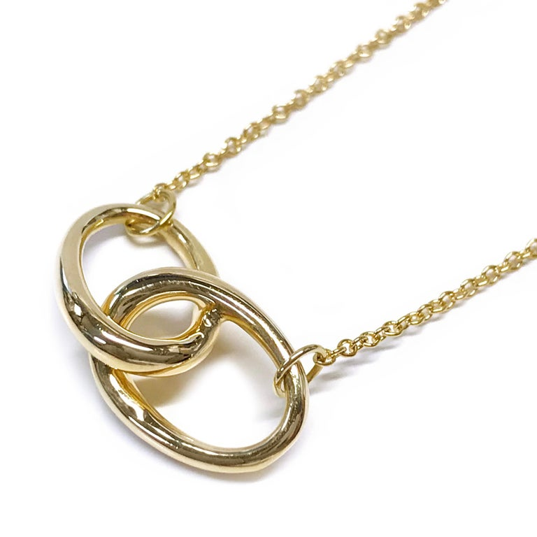 Tiffany & Co. Elsa Peretti Vintage 18 Karat yellow gold interlocking ovals pendant necklace. The pendant measures 19.75mm wide and 9.8mm high. Stamped on one pendant oval is Tiffany & Co. and on the other oval Perreti 750. The necklace is 16
