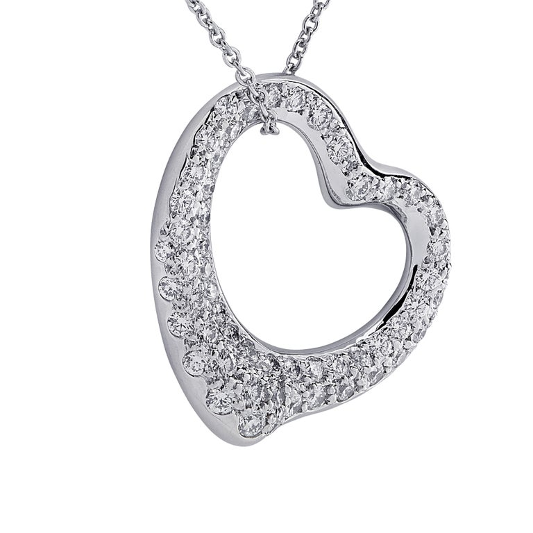 Enchanting Tiffany & Co. Elsa Peretti Spain open heart diamond pendant crafted in 18 Karat white gold, featuring 22 round brilliant cut diamonds, graduating in size, weighing approximately .40 carats total, G color, VS clarity. The pendant measures