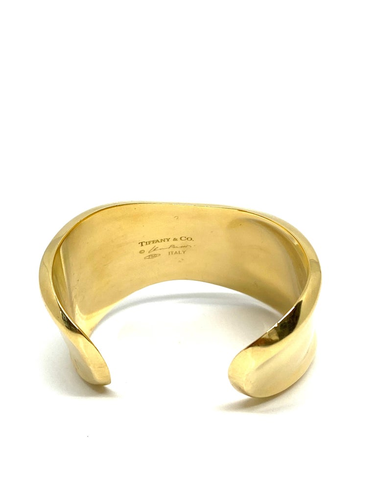 Product details: 18K yellow gold 43mm wide Opening is 26mm Inner circumference is 5.75