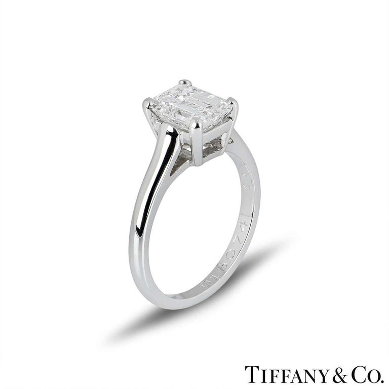 A stunning emerald cut diamond single stone ring in platinum by Tiffany & Co. The ring is set to the centre with a 1.59ct emerald cut diamond, E colour and VS1 in clarity, set within a four claw setting. The ring is currently a size UK J½ - EU 49 -