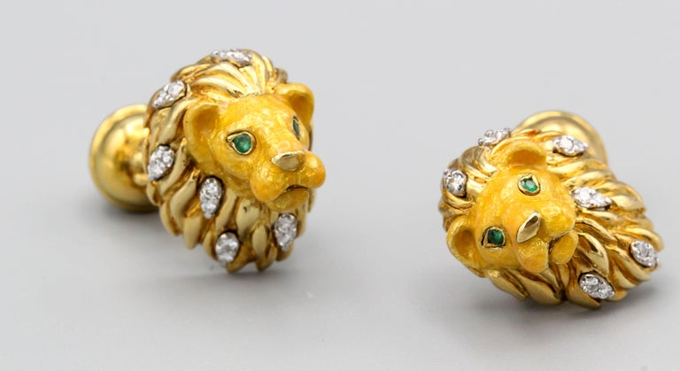 Handsome 18K yellow gold cufflinks by Tiffany & Co. They resemble a lion heads with round cut emerald eyes, diamonds in the mane, enameled face, and the opposite end with a paw on top of a sphere coming out of the back.   Hallmarks: Tiffany & Co.