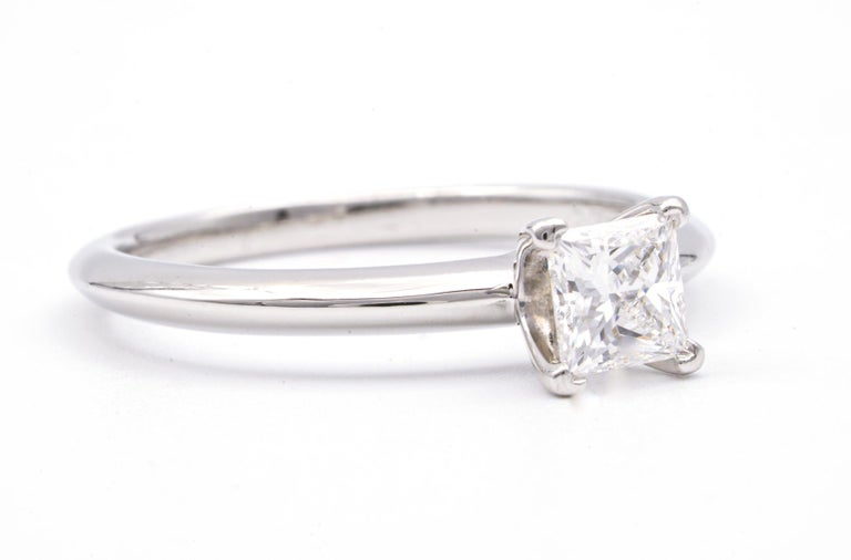 Classic Diamond Engagement Solitaire ring signed by Tiffany & Co. featuring a 4 prong set 0.54 ct Center princess cut diamond in platinum. Graded by Tiffany E color , and VS2 Clarity. Includes Original Tiffany Certificate and Box  Crown Inscription