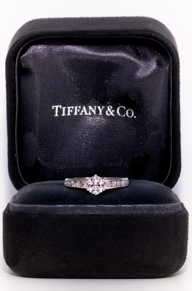 Tiffany & Co Diamond Engagement Solitaire signed by Tiffany & Co. featuring a .71 carat Center, graded G Color , and VS2 Clarity. Highlighted with 10 Channel set brilliant cut round diamonds weigh approximately .35 Cts Total Includes original