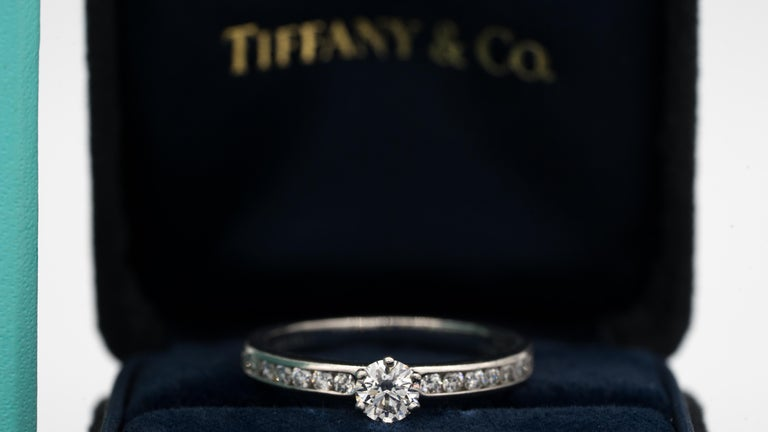 Tiffany & Co. Diamond Engagement Ring with Channel Set Diamond band signed by Tiffany & Co. featuring a .30 ct Center, graded by Tiffany G color , and VVS2 Clarity In Platinum.  Center diamond is flanked on each side by 7 diamonds , for a total of