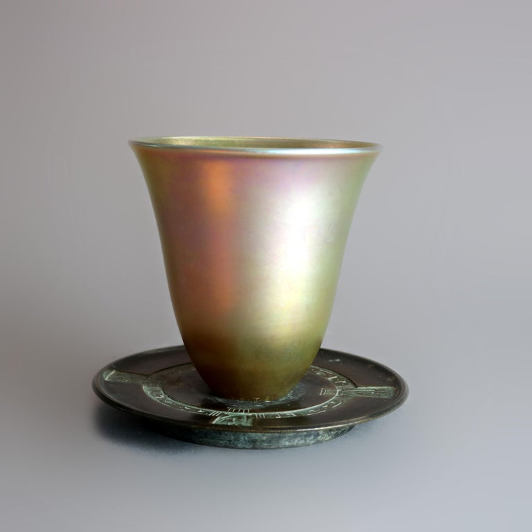 An antique Egyptian Revival libation cup by Tiffany & Co. offers flared Favrile art glass vessel seated on cast bronze base with repeating design having symbols and stylized figures, stamped on base as photographed, circa 1890