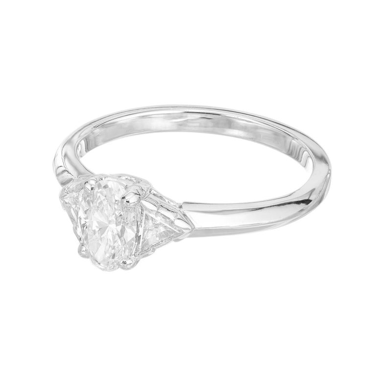 Tiffany & Co Platinum oval engagement ring. GIA certified oval center stone in a platinum three-stone setting with two trilliant cut side diamonds. Diamond removed and reset for GIA certification.   1 GIA certified oval diamond, 0.58 cts, D, VS1,