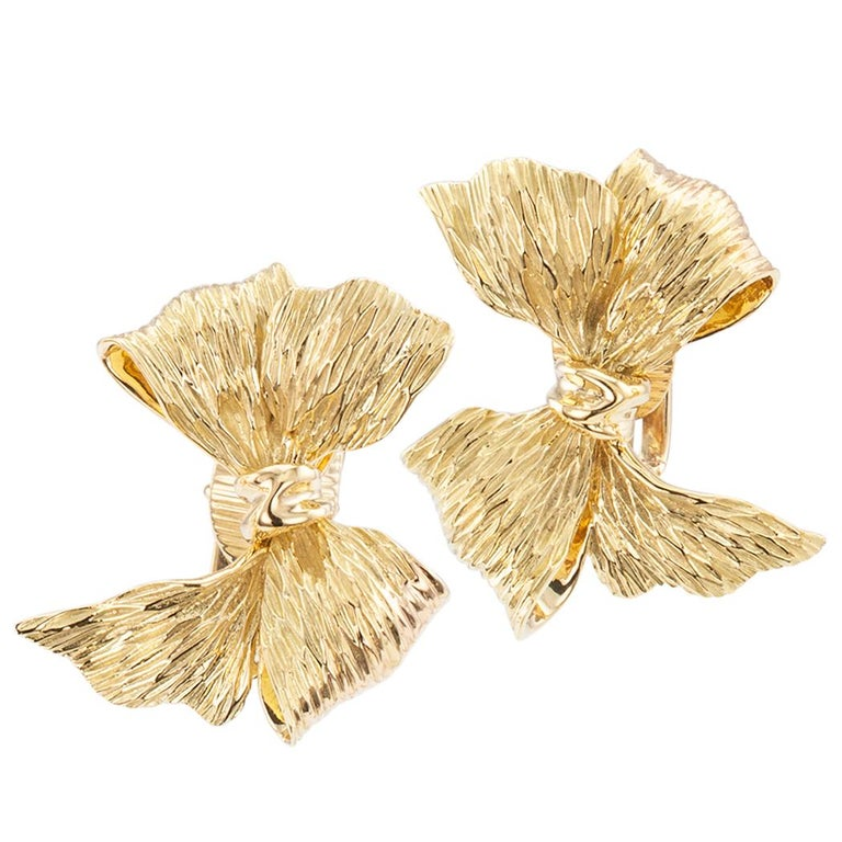 Tiffany & Co. gold bow earrings circa 1960. The matching left and right designs comprise a pair of dimensional and textured gold bows crafted in    18 karat yellow gold with clip backs, signed Tiffany & Co. Very pristine condition consistent with