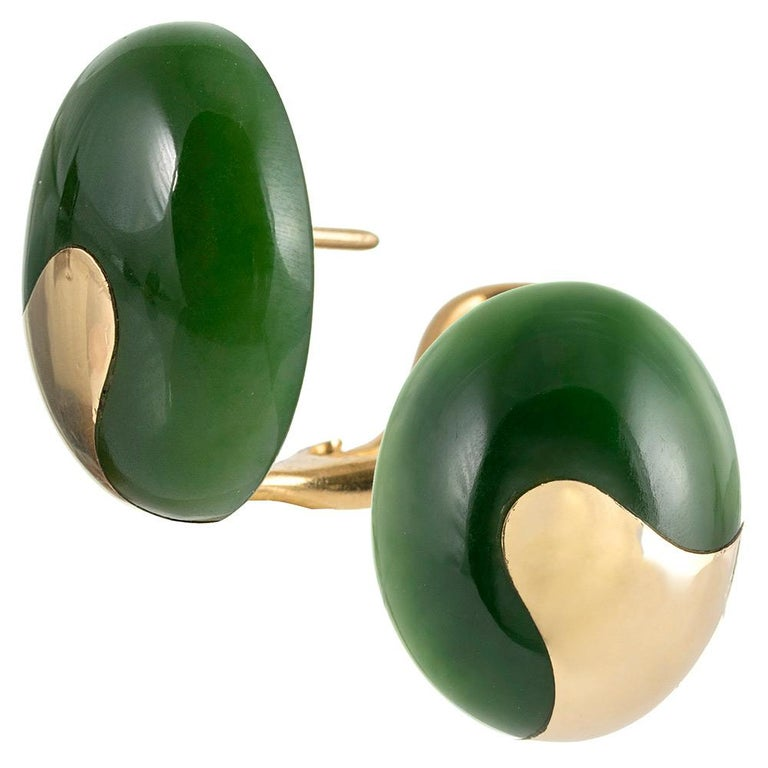 Two cabochons of jade are enhanced by their stylized golden mounting, as it is integrated into the design. Made of 18 karat yellow gold and fitted for pierced ears, they can be converted to clips on request. 7/8 x 5/8 inches.