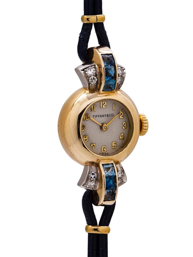 Vintage lady's Tiffany & Co. 14K YG dress watch circa 1940's. Beautiful design model with small distinctive dome shaped Cressarrow signed case and extended, curved triple pronged lugs, set with diamonds and sapphires. With contemporary cord leather