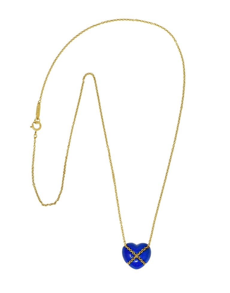 Classic cable chain necklace centers a lapis lazuli heart cabochon  Opaque and is uniformly ultramarine blue in color  Tightly wrapped with cable chain in an X motif  Necklace completes as a spring ring clasp  Logo link is stamped 750 for 18 karat