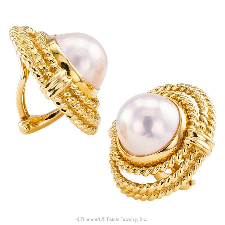 Tiffany & Co mabe pearl and gold clip on earrings circa 1990. Featuring a pair of mabe pearls measuring approximately 12 mm, bezel-set in an oval-shaped stepped border of cable gold, omega clip backs, mounted in 18-karat yellow gold, signed Tiffany