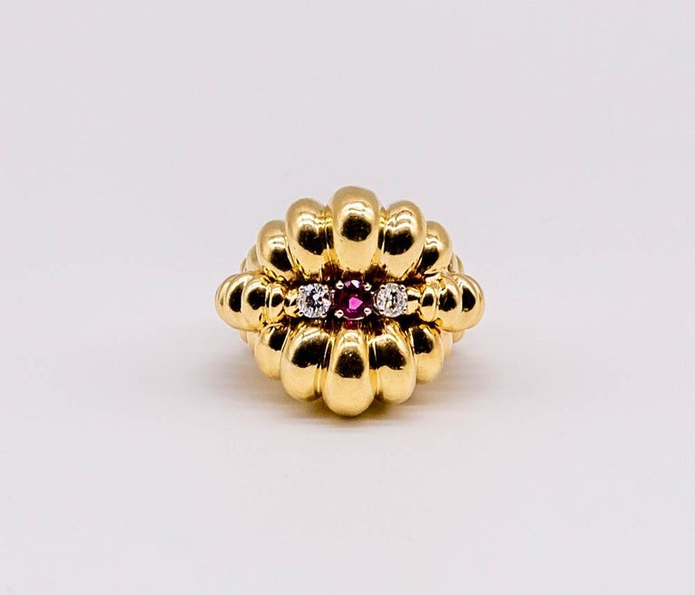 A strong statement piece, this distinctive ring consists of geometrically placed domes of 18 karat yellow gold centering a round ruby flanked by round diamonds.  The ring is a wearable size 6 1/4, and the round ruby weighs about 1/2 carat.  (we do