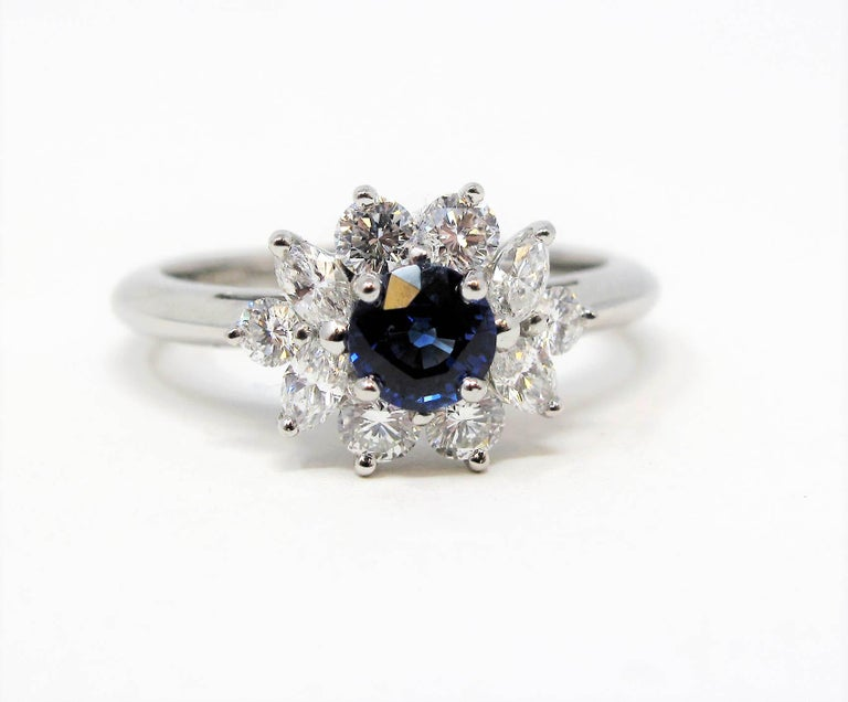 Absolutely radiant natural sapphire and diamond halo ring from esteemed jeweler, Tiffany & Co.. The vivid blue center stone is paired with a glittering halo of bright white diamonds, allowing this beautiful, feminine piece to sparkle spectacularly