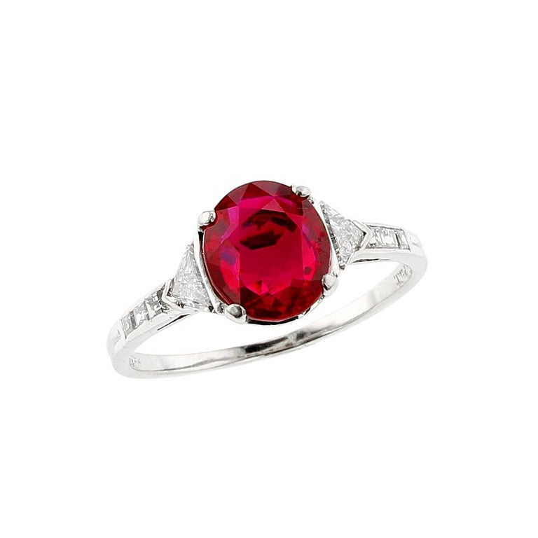 A beautiful and classic Tiffany & Co. platinum ring centered with a two-carat, oval-shape natural, no-heat Burma (Myanmar) ruby, tapered with two triangular-shaped diamonds with a shoulder accented with Asscher cut diamonds. The ruby accompanies a