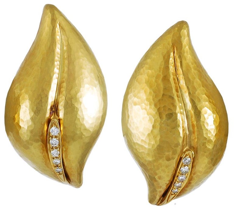 Designed as finely sculpted leaves of an olive branch, this elegant pair of vintage 18k yellow gold ear clips and matching brooch crafted with a pavé of round brilliant diamonds that dazzle within the leaves. Signed Paloma Picasso by Tiffany &