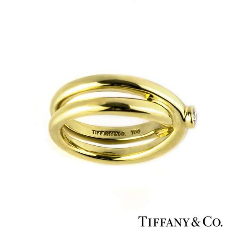 An 18k yellow gold diamond ring from the Tiffany & Co. Paloma Picasso collection. The ring is composed if a single round brilliant cut diamond weighing 0.10ct, colour G and VS clarity, set within a rub over setting. The stone is set to the centre of