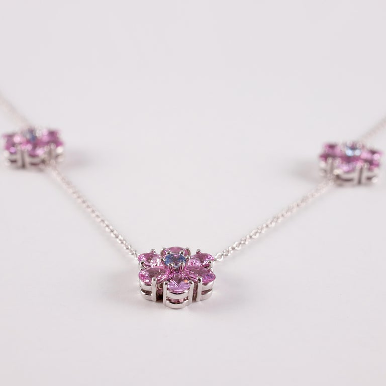 A fun and flirty look for any age!! This platinum, interlocking link necklace is secured with a spring ring clasp and suspends flower three stations that support a total of 3.00 carats pink sapphires and 0.15 carats blue sapphires .