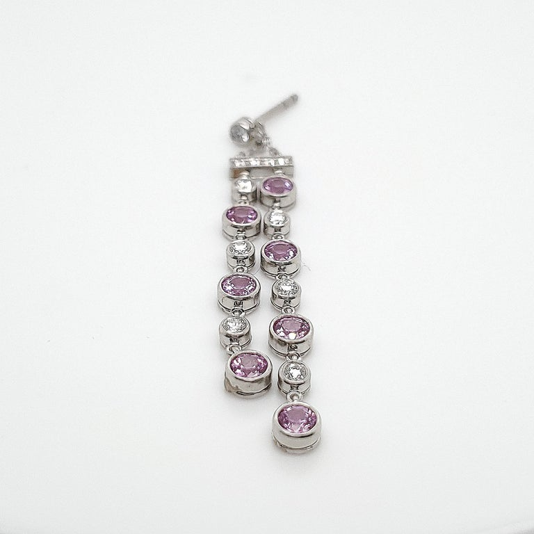 Authentic Tiffany & Co. earrings made in platinum with pink sapphires and approximately 22 round brilliant diamonds.  This delicate 2 strand design measures 2 inches in length.  CIRCA 21st Century.  Signed T & Co. PT950