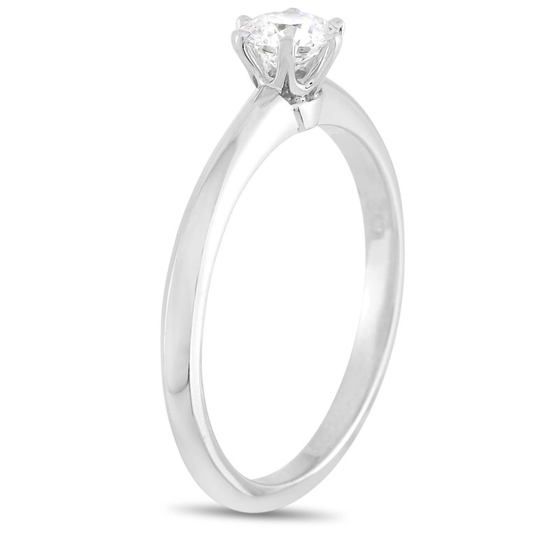 Lovers of classic lines will be attracted to the dainty silhouette of this ring. The Tiffany & Co. Setting Platinum 0.30 ct Diamond F-VS1 Engagement Ring (3.3g) exudes a timeless appeal honored for its elegant simplicity. The round brilliant diamond