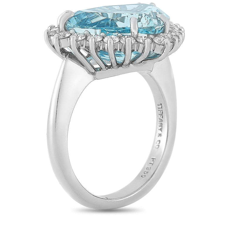This Tiffany & Co. ring is crafted from platinum and weighs 11.4 grams, boasting band thickness of 3 mm and top height of 8 mm, while top dimensions measure 19 by 15 mm. The ring is set with a 5.50 ct aquamarine and a total of 1.00 carat of