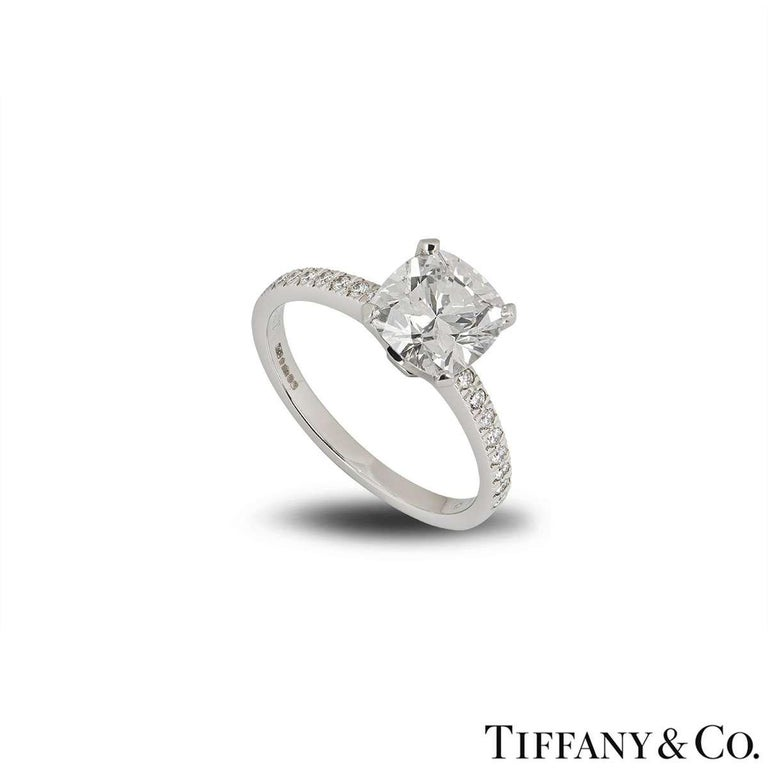 An eye-catching diamond ring in platinum from the Novo collection by Tiffany & Co. The ring is set to the centre with a 2.22ct cushion cut diamond in a classic 4 claw setting. The diamond is G colour and VVS1 clarity. Set to either side of the