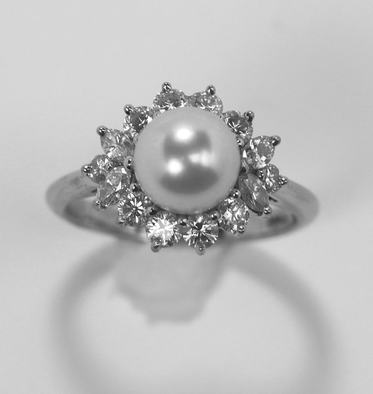 A platinum ring by Tiffany and Company centered around an 7.7 mm pearl in a classically  inspired ballerina style setting, with 0.85 carats of round brilliant cut and marquise cut  diamonds of overall F Color and VVS1 Clarity. The pearl is white