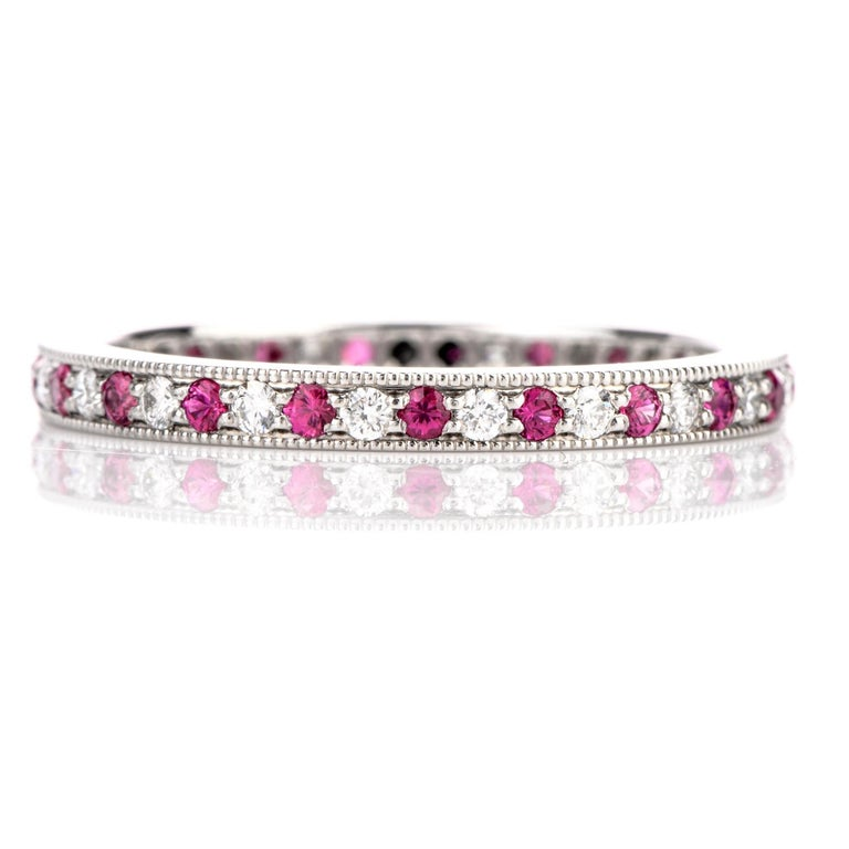 This Timeless Legacy Collection Tiffany and Co Diamond and Pink Sapphire Eternity Band is crafted in   luxurious Platinum . Alternating completely around this ring are prongset Diamonds and Pink Sapphire cuddled by  a soft beaded edge to finish the