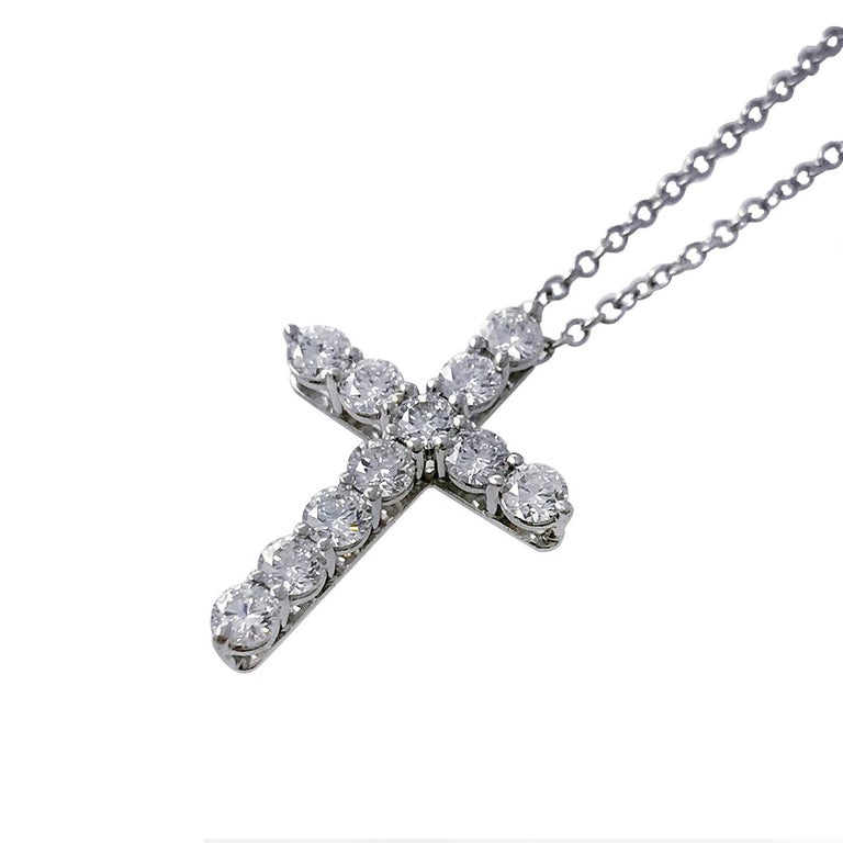 Tiffany & Co. platinum diamond cross pendant necklace adorned with eleven round brilliant cut diamonds. The diamonds are prong-set in basket-style mountings that allow light to flow through the diamonds for ultimate sparkle and brilliance. Diamonds