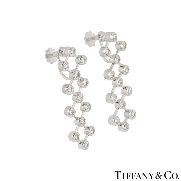 A stunning pair of platinum diamond drop earrings by Tiffany & Co. The earrings are set with round brilliant cut diamonds in a rubover setting joined together by moving flexi bars. The 26 diamonds have an approximate total weight of 1.04ct. The
