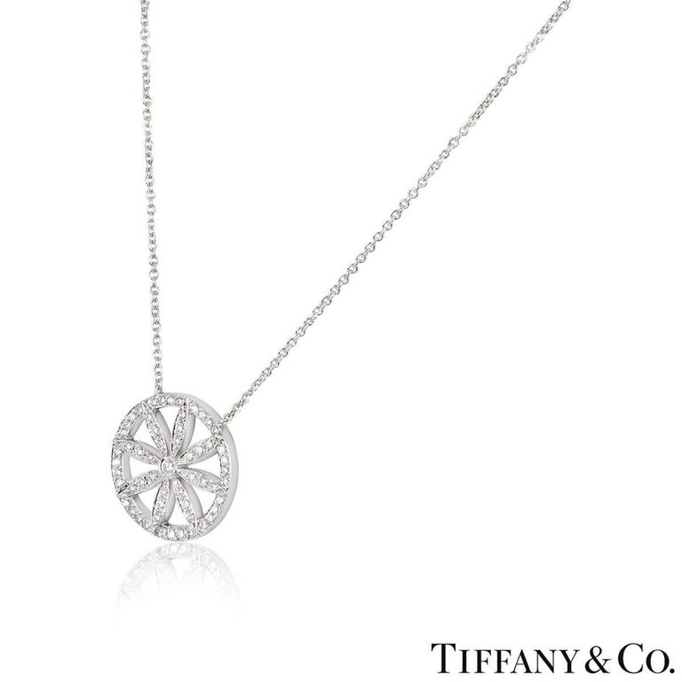 A beautiful platinum flower necklace by Tiffany & Co. The necklace features an openwork diamond set circular motif with a flower in the centre. There are 57 round brilliant cut diamonds with a total diamond weight of approximately 0.61ct. The motif
