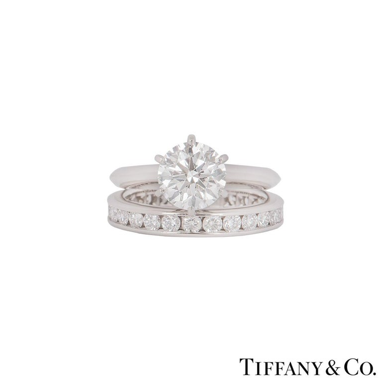 A stunning platinum diamond ring with a full diamond eternity ring by Tiffany & Co. The ring features a round brilliant cut diamond in a 6 claw setting with a weight of 1.61ct, I colour and VS2 clarity.  The diamond scores an excellent rating in all