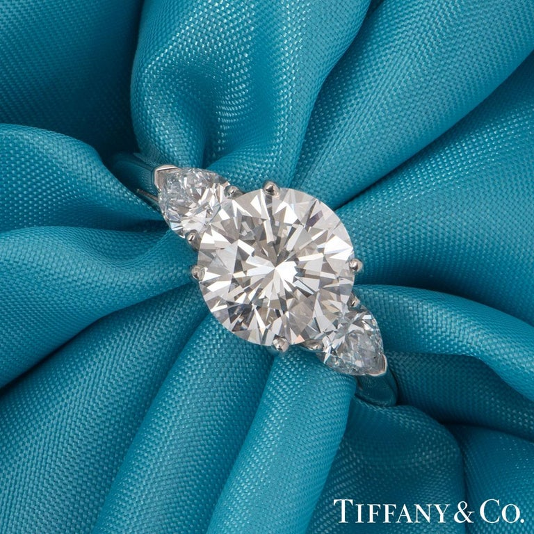 A stunning three stone ring in platinum by Tiffany & Co. The ring is set to the centre with a 2.36ct round brilliant cut diamond, E colour and VVS2 in clarity set within a four claw setting. Beside the central stone are two pear cut diamonds set to