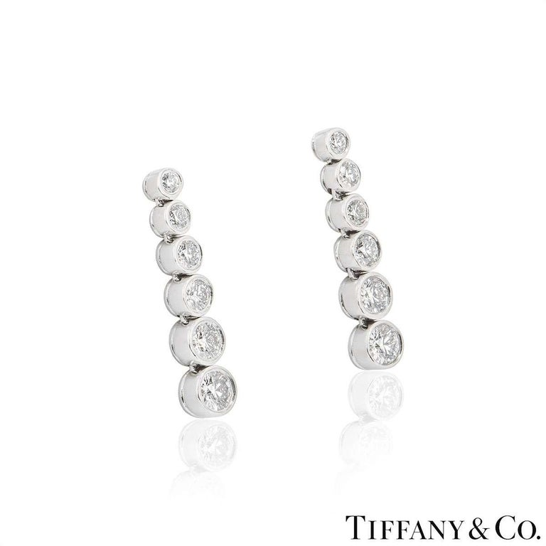 A beautiful pair of platinum earrings from the Jazz collection by Tiffany & Co. Each earring has 6 rubover set diamonds in a vertical drop graduating in size. The diamonds have a total weight of approximately 1,20ct. The earrings measure 1.2cm in