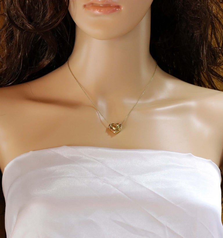 A ladies 18 karat yellow gold puffed heart pendant featuring a beaded edge suspended on a 15 inch 18K gold, cable link chain. The heart measures 5/8
