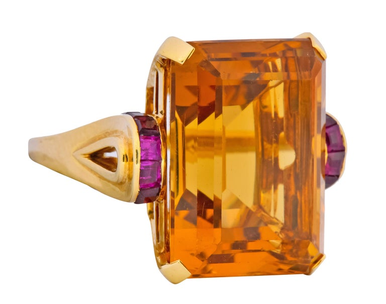 Centering a basket set rectangular step cut citrine weighing approximately 23.90 carats, transparent and a medium-dark orangey-yellow   Flanked by channel set calibré cut rubies weighing approximately 0.64 carat total, very well matched and a