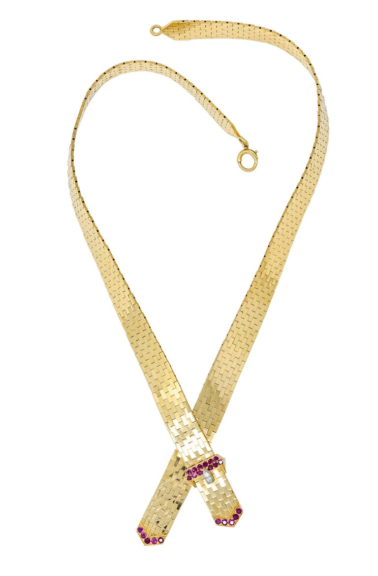 Collar necklace is comprised of polished gold brick links, incredibly malleable  Centering a buckle motif with two suspended tails  Accented by round cut ruby and round brilliant cut diamonds; purplish-red and bright white  Weighing in total
