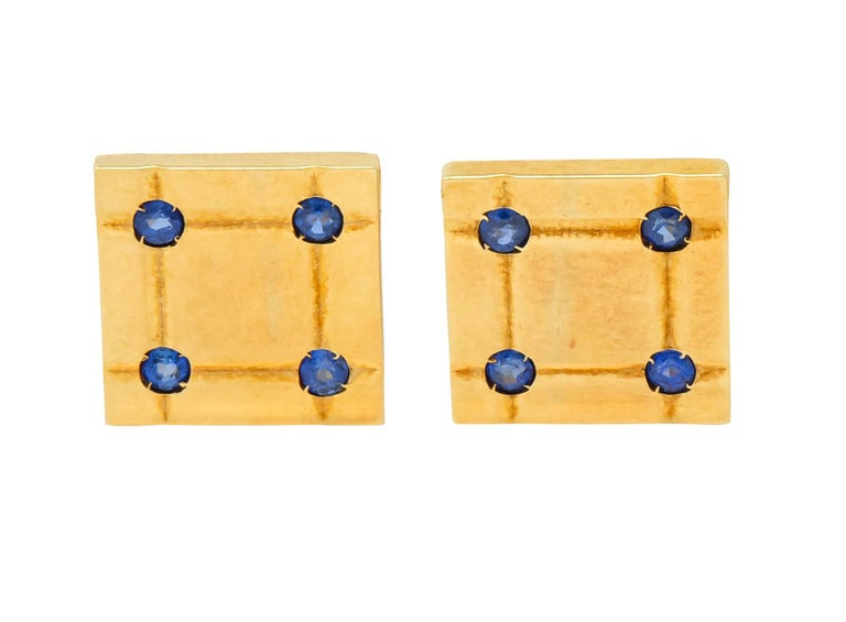 Lever style cufflinks designed as a deeply grooved polished square  With three matching, spring loaded, bar shirt studs  Each accented by four round cut sapphires weighing approximately 0.96 carat total, very well-matched and a bright denim blue