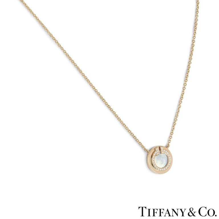 An 18k rose gold pendant from the Tiffany T collection by Tiffany & Co. The pendant comprises of a mother of pearl disk in the centre surrounded by a boarder of round brilliant cut diamonds. There are 28 diamonds with a total weight of 0.03ct. The